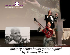 Courtney Krupa holds guitar signed by Rolling Stones