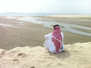 Lone arab on desert dune photo